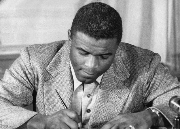 """NEW YORK, UNITED STATES:  (FILES)This undated file photo shows US baseball star Jackie Robinson as he signs a then-record contract to play for the Brooklyn Dodgers in New York. Robinson has been chosen to receive posthumously the Congressional Gold Medal, the highest award Congress can bestow on a US civilian, 02 March 2005, for his accomplishments on the baseball diamond, as well as """"his lifetime of breaking down barriers and his unending fight for justice,"""" officials on Capitol Hill said in an earlier press release. US Senator John Kerry and US Representative Richard Neal, who co-sponsored legislation honoring Robinson, will be joined by the ballplayer's widow Rachel Robinson, US President George W. Bush and congressional leaders at the ceremony. Robinson broke baseball's """"color line"""", becoming the first African American to play in the Major Leagues when he debuted with the Brooklyn Dodgers in 1947. Officials in Congress said however that he is also being honored for his contributions to the broader struggle for civil rights."""