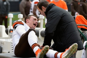 A trainer tends to Johnny Manziel #2 of the Cleveland Browns after he was imjured during their game against the Carolina Panthers at Bank of America Stadium on December 21, 2014 in Charlotte, North Carolina. (Photo by Grant Halverson/Getty Images)